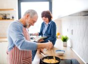 A portrait of happy senior couple in love indoors at home, cooking.