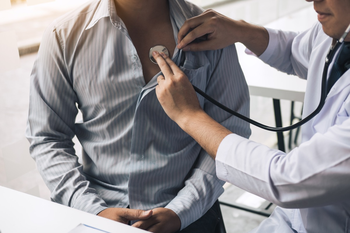 doctor is using a stethoscope listen to the heartbeat of the elderly patient.
