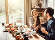 young couple sitting on a table and having breakfast together