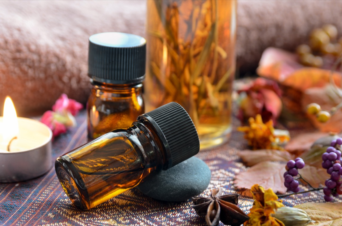 essential oils in amber bottles next to dried flowers
