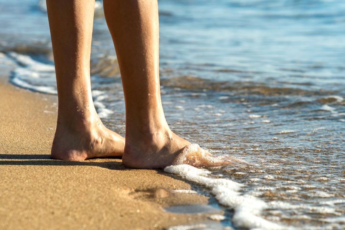 woman's feet in ocean water
