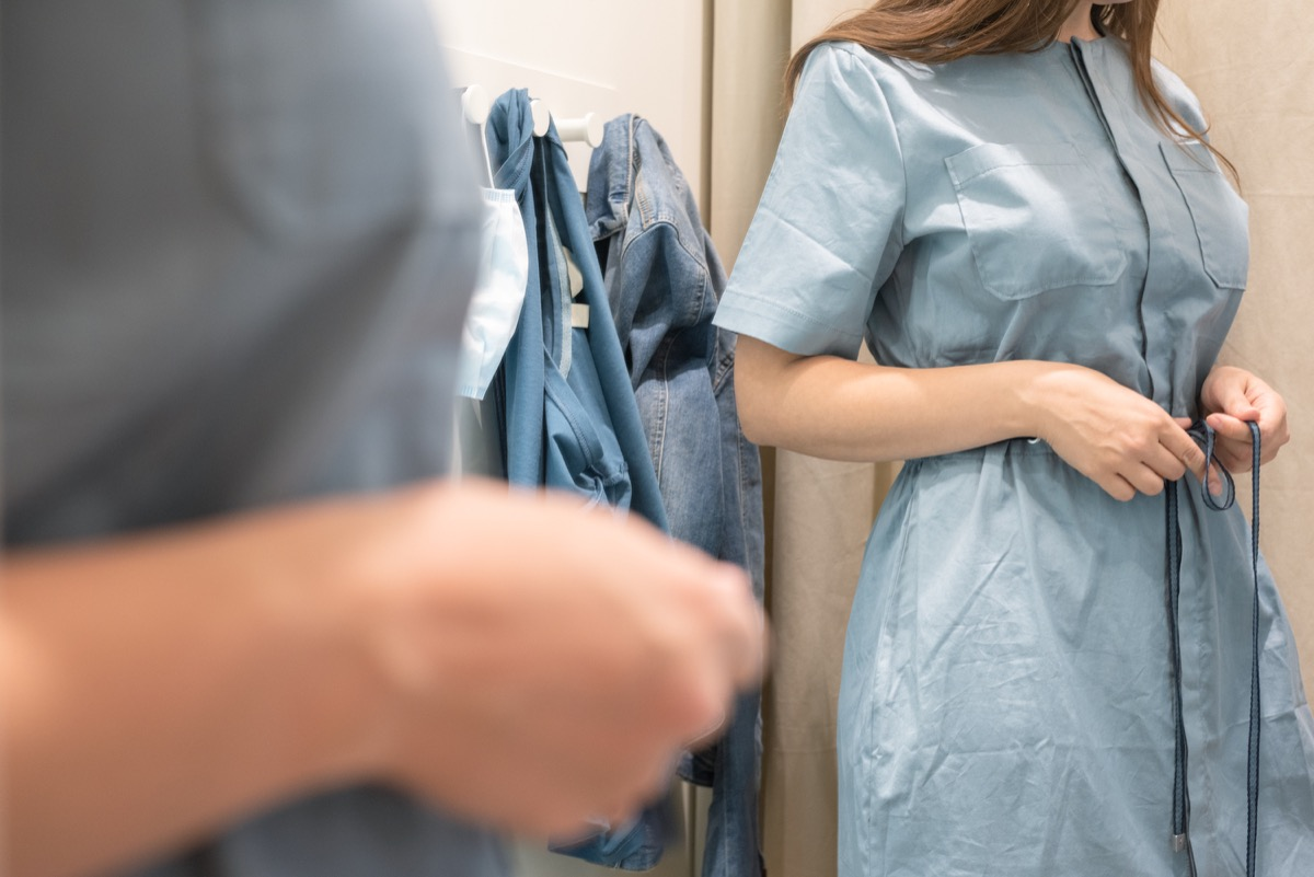 Woman trying on a blue dress in a store.
