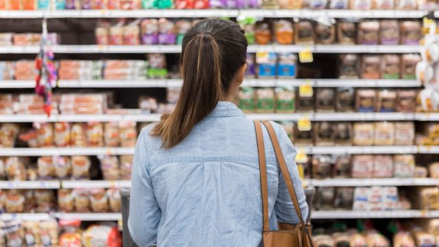 In this rear view, an unrecognizable woman stands with a shopping cart in front of a shelf full of food in the bread aisle of a grocery store.