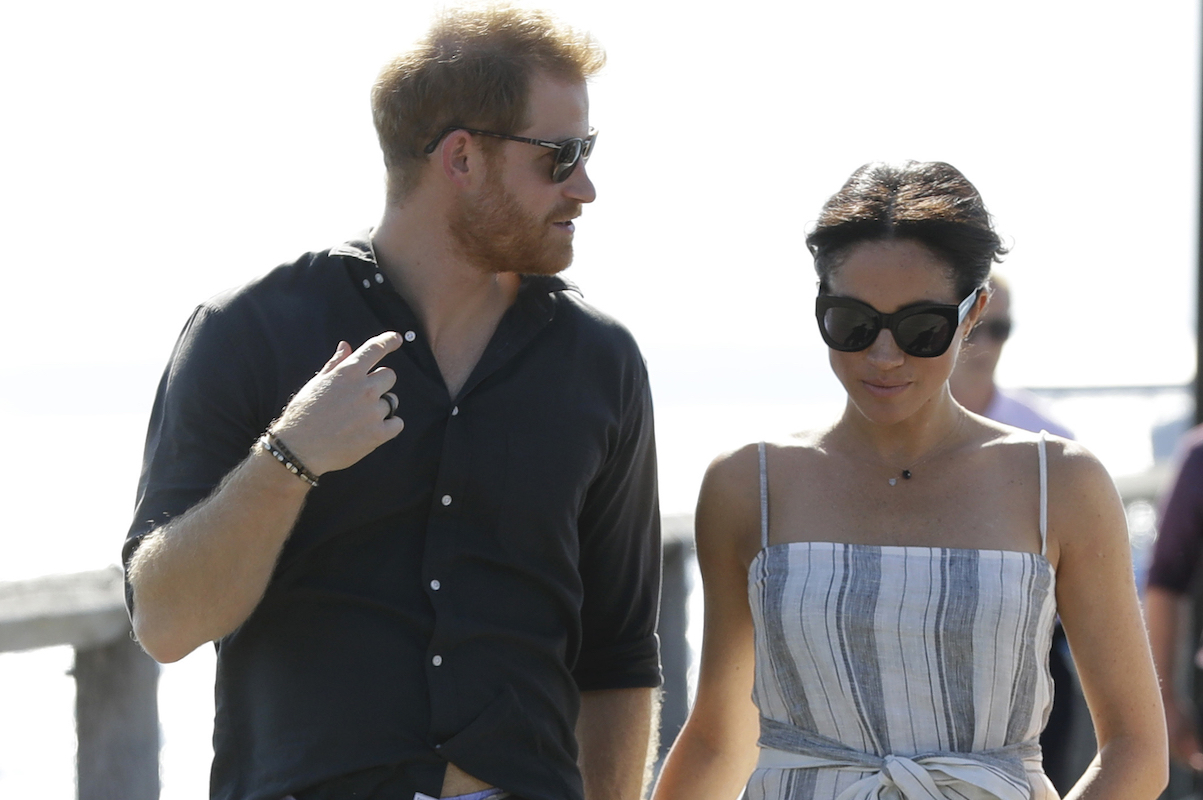 Britain's Prince Harry and Meghan, Duchess of Sussex walk along Kingfisher Bay Jetty during a visit to Fraser Island, Australia, Monday, Oct. 22, 2018