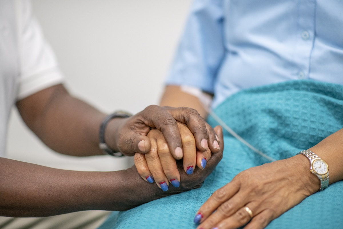 Elderly woman is comforted by a medical professional during the Covid-19. Focus is on their hands. The medical staff is holding the woman's hand.