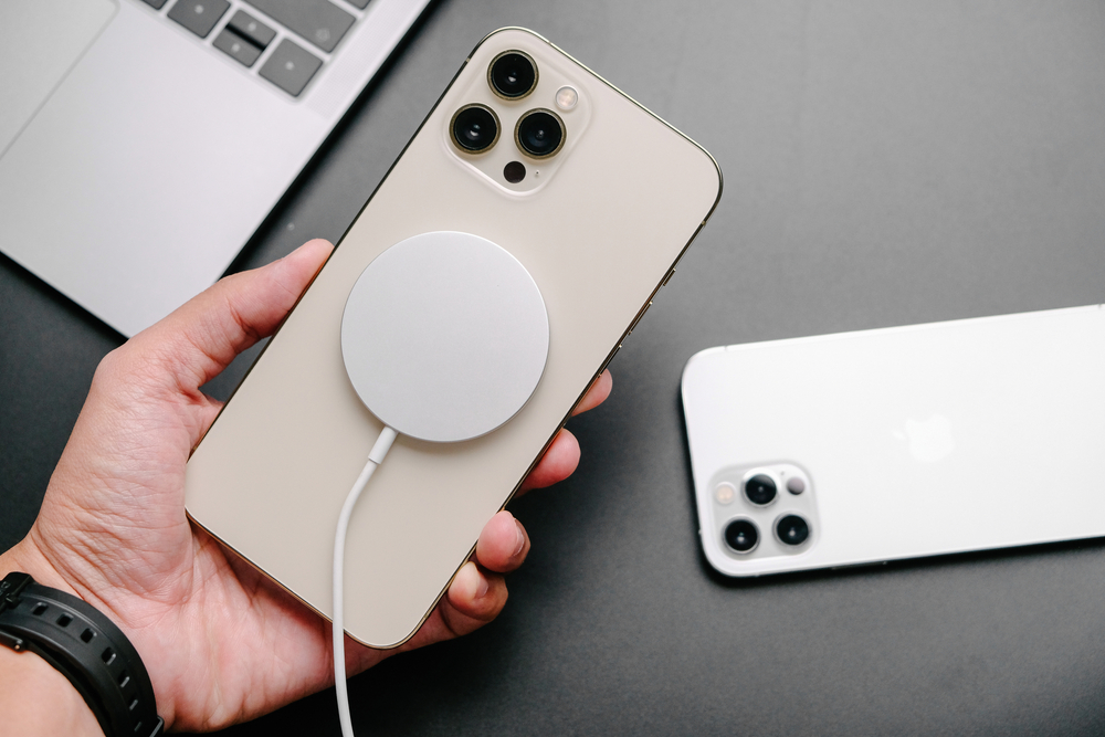 A hand holding an iPhone 12 that is hooked up to a MagSafe charging device