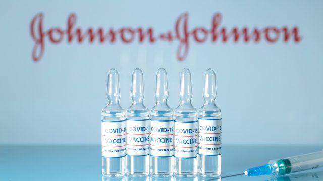 A se of 5 vials of Johnson & Johnson COVID-19 vaccine in front of the company's logo