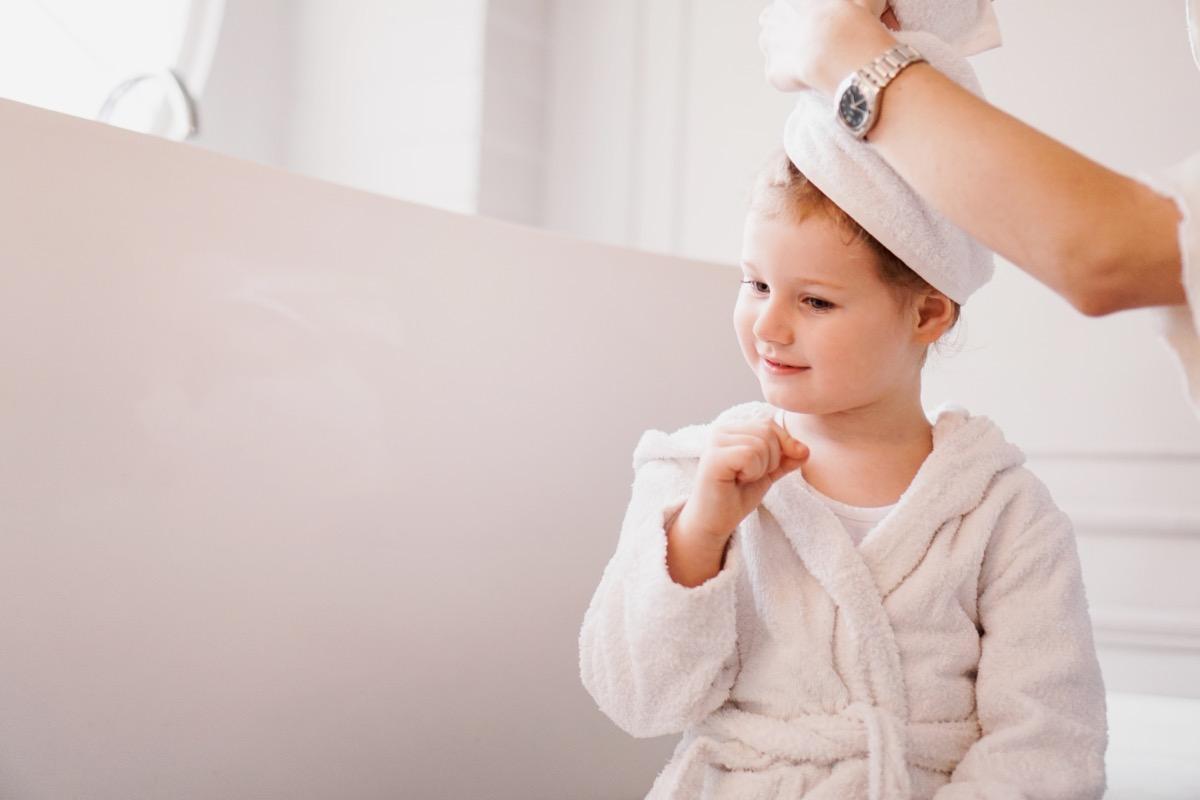 kid in white bathrobe with towel on hair