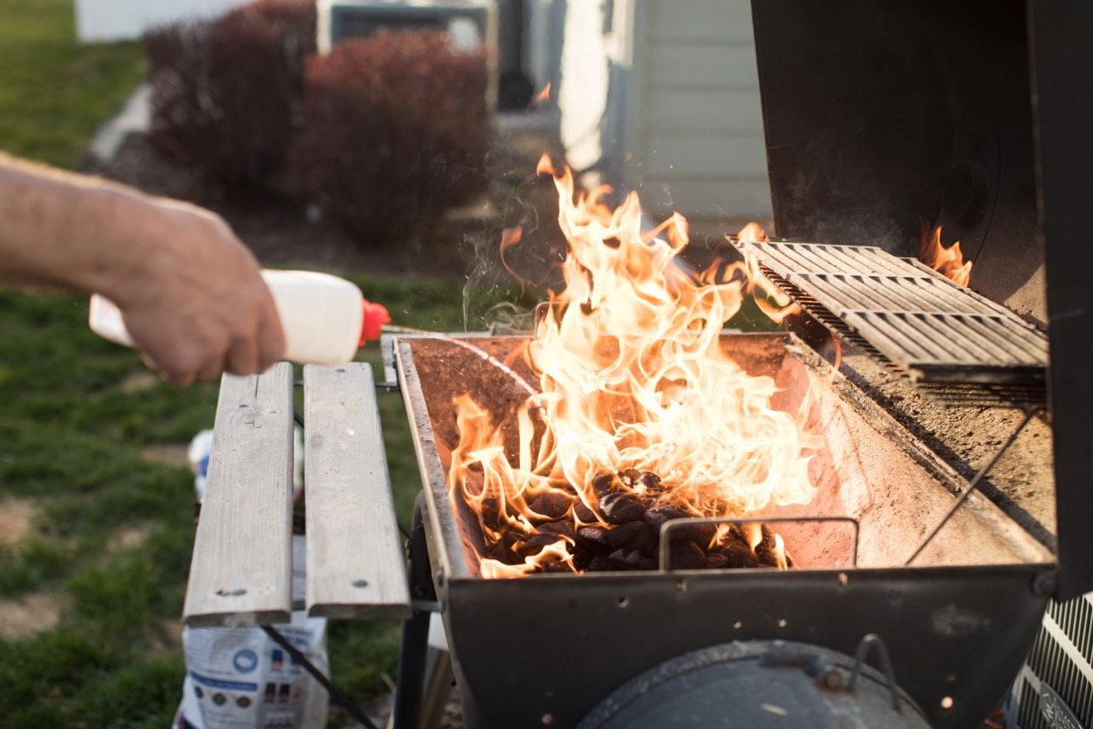 pouring lighter fluid on grill