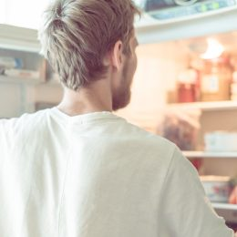 young man searching for food in fridge at home