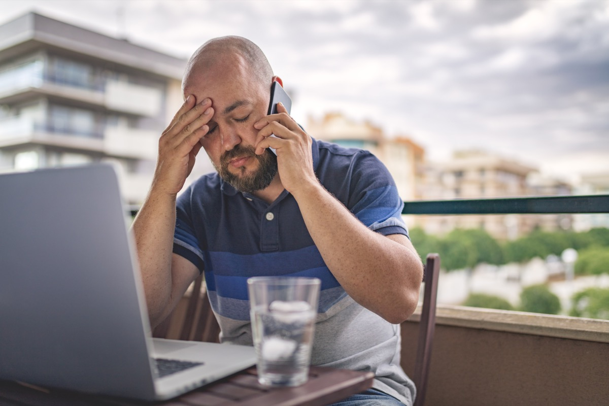 Worried and exhausted male talking on phone at balcony