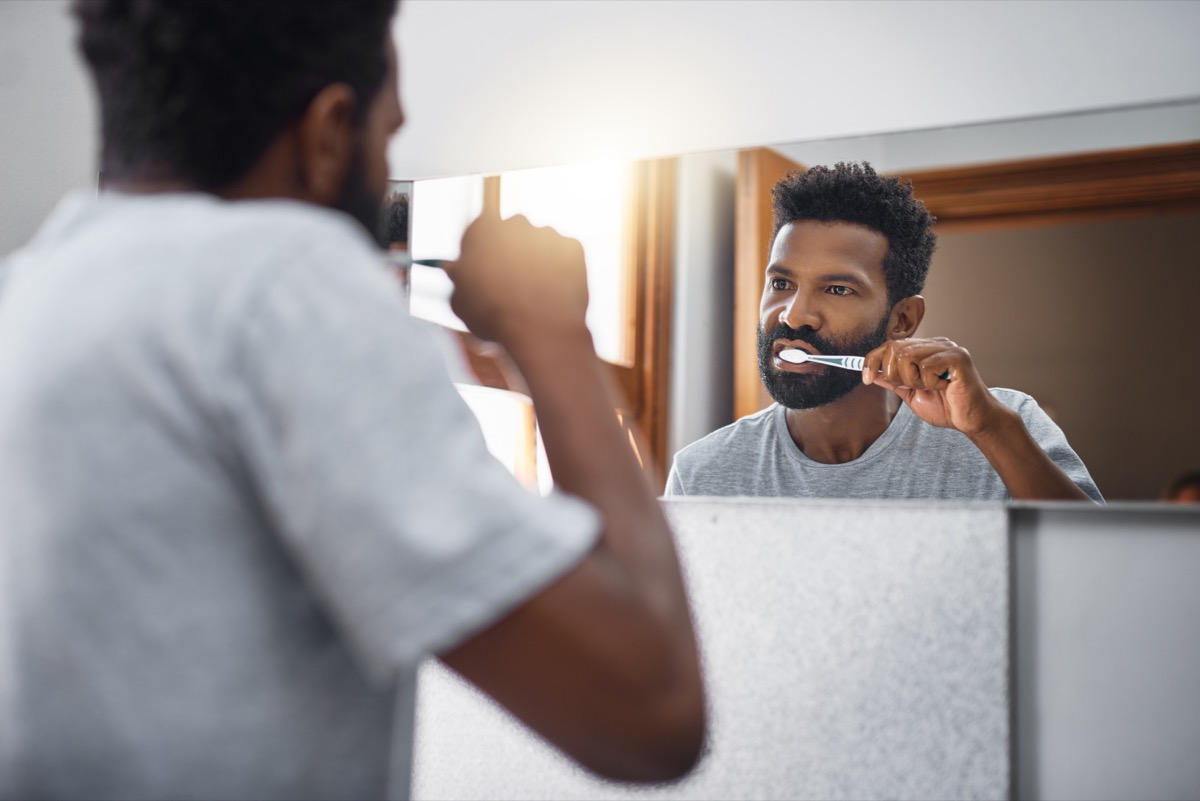 Cropped shot of a handsome young man brushing his teeth in the bathroom at home