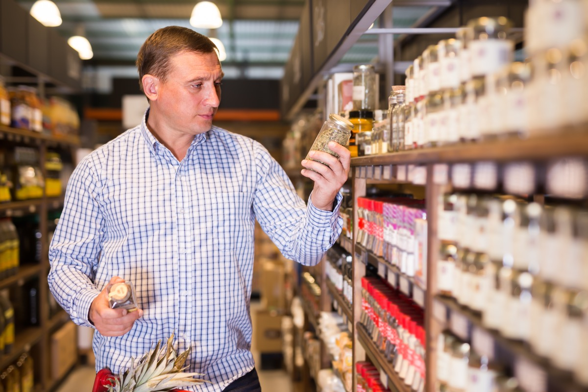 man buying spices in grocery store