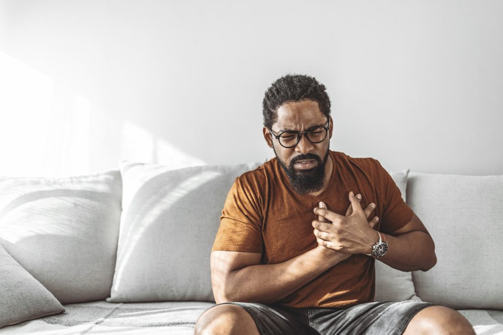Man with high blood pressure experiencing chest pain while sitting at home during the day.