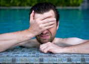 A young man in the pool covers his face with his hand.