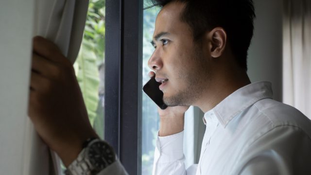 man talking on cell phone looking out window