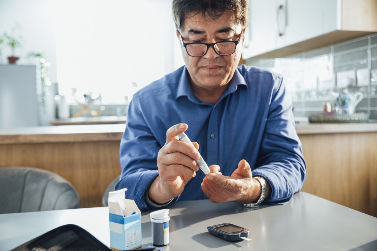 man sitting at a dining table in his kitchen, he is pricking his finger using a glaucometer to test his blood sugar levels, he is managing his diabetes.