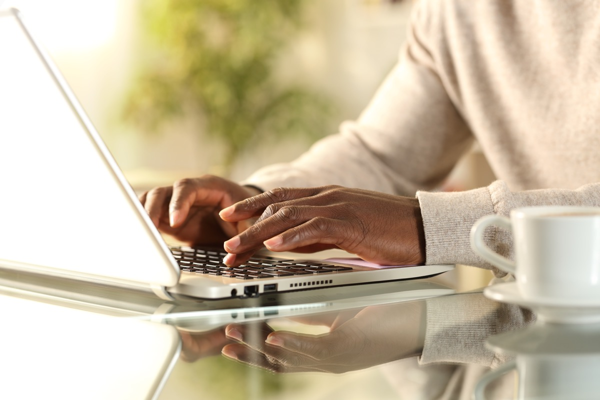man hands typing on a laptop at home