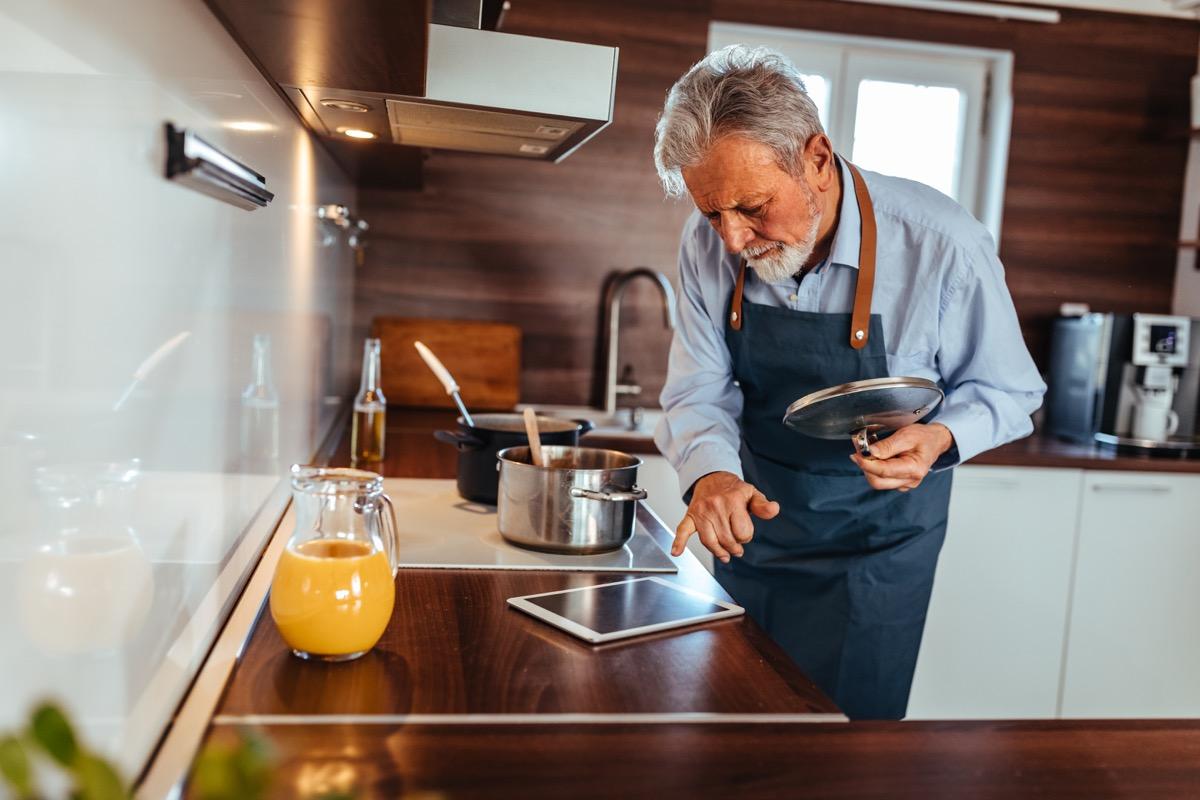 Senior man preparing delicious meal in the kitchen