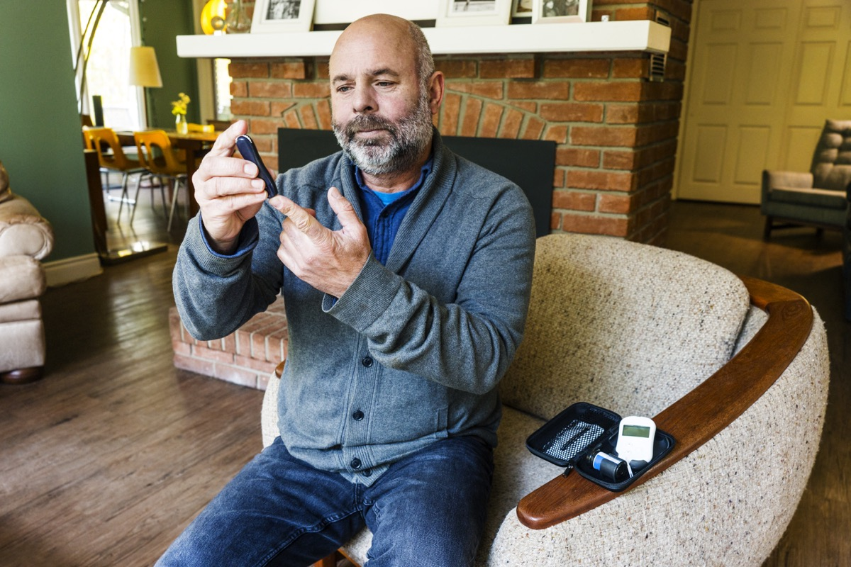 A mature man in his fifties at home testing his blood sugar levels.