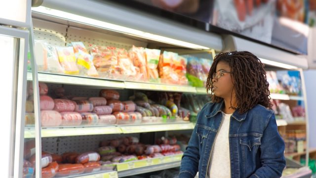 woman wheeling shopping cart in grocery store, looking at sausages and ham. Buyer shopping in supermarket. Food shop concept