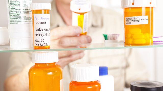 Senior adult man gets prescription medicines out of his medicine cabinet. Close up of hands and pills.