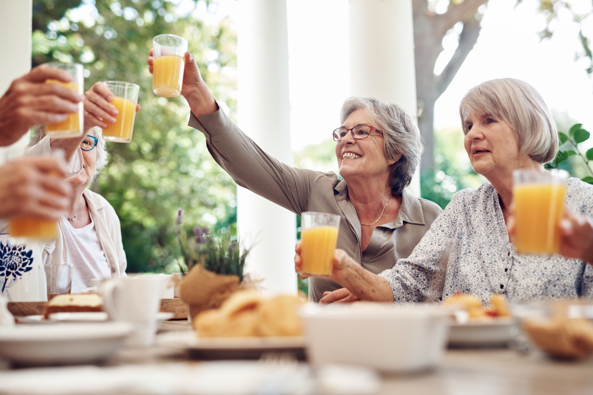 Cropped shot of a group of seniors sitting together and raising their fruit juice glasses for a toast