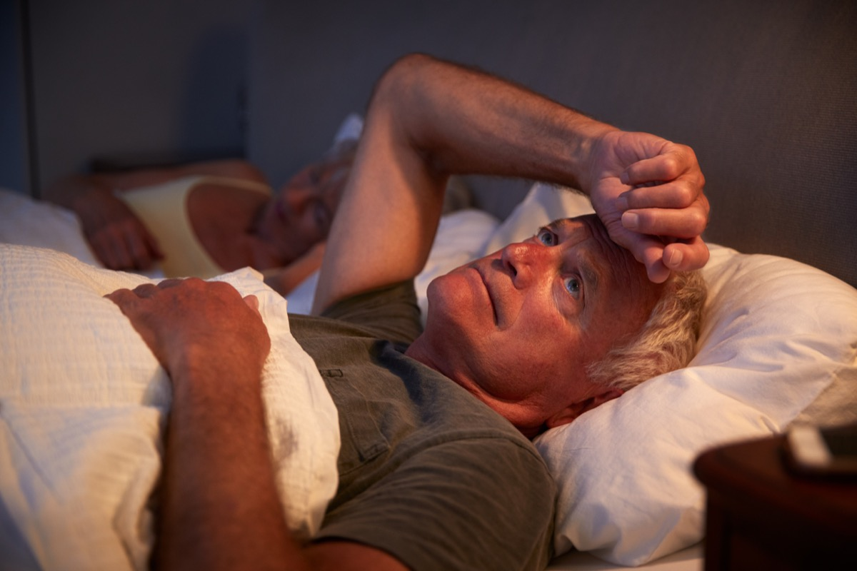older man with gray hair awake in bed at night