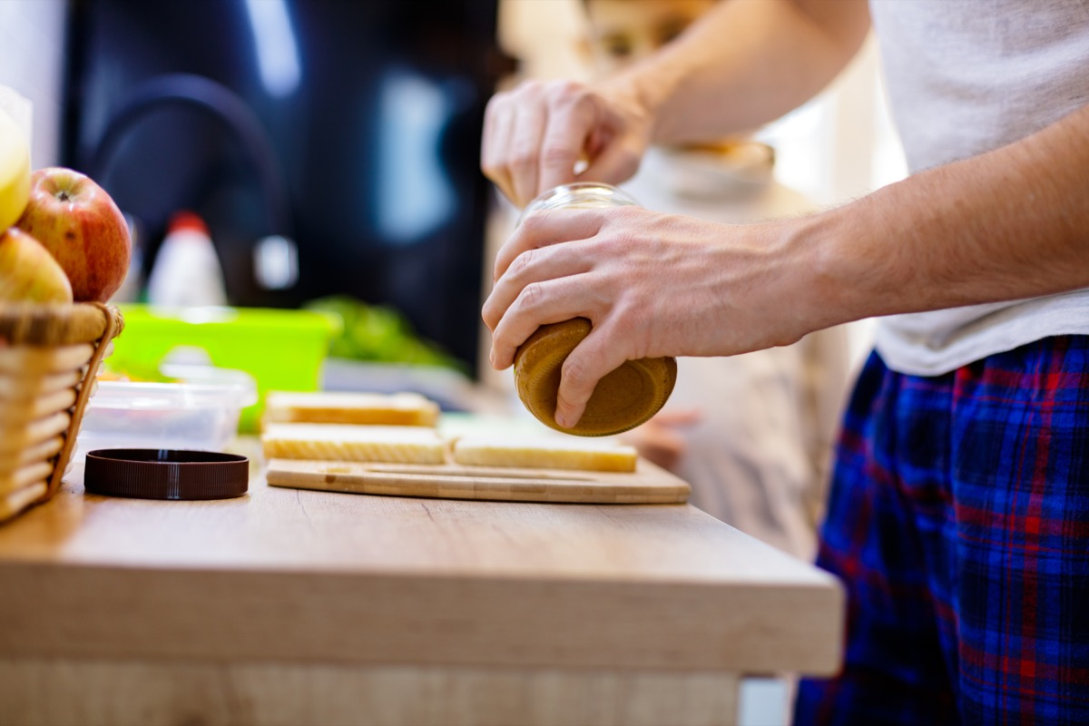 Close-up of unrecognizable father making peanut butter sandwiches for his 6 year old son