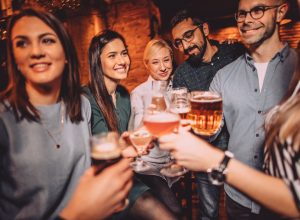 A group of friends raising a toast with drinks in a bar