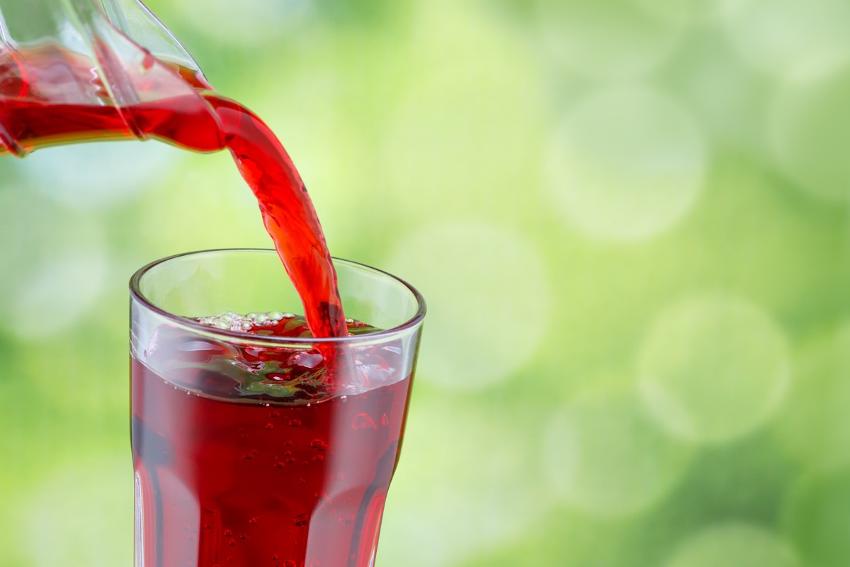 pouring cherry juice into clear glass
