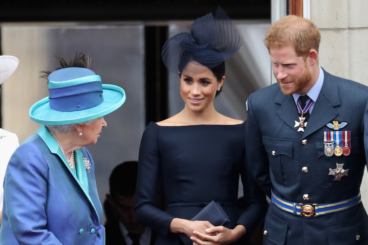 Queen Elizabeth II, Meghan, Duchess of Sussex, Prince Harry, Duke of Sussex watch the RAF flypast on the balcony of Buckingham Palace