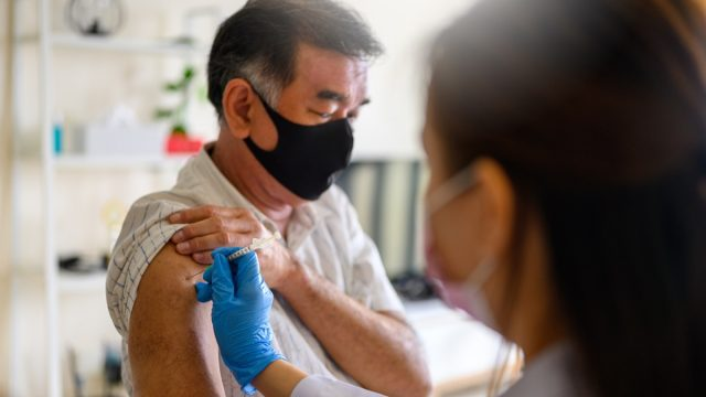 female doctor working with the syringe for vaccination with a senior man.