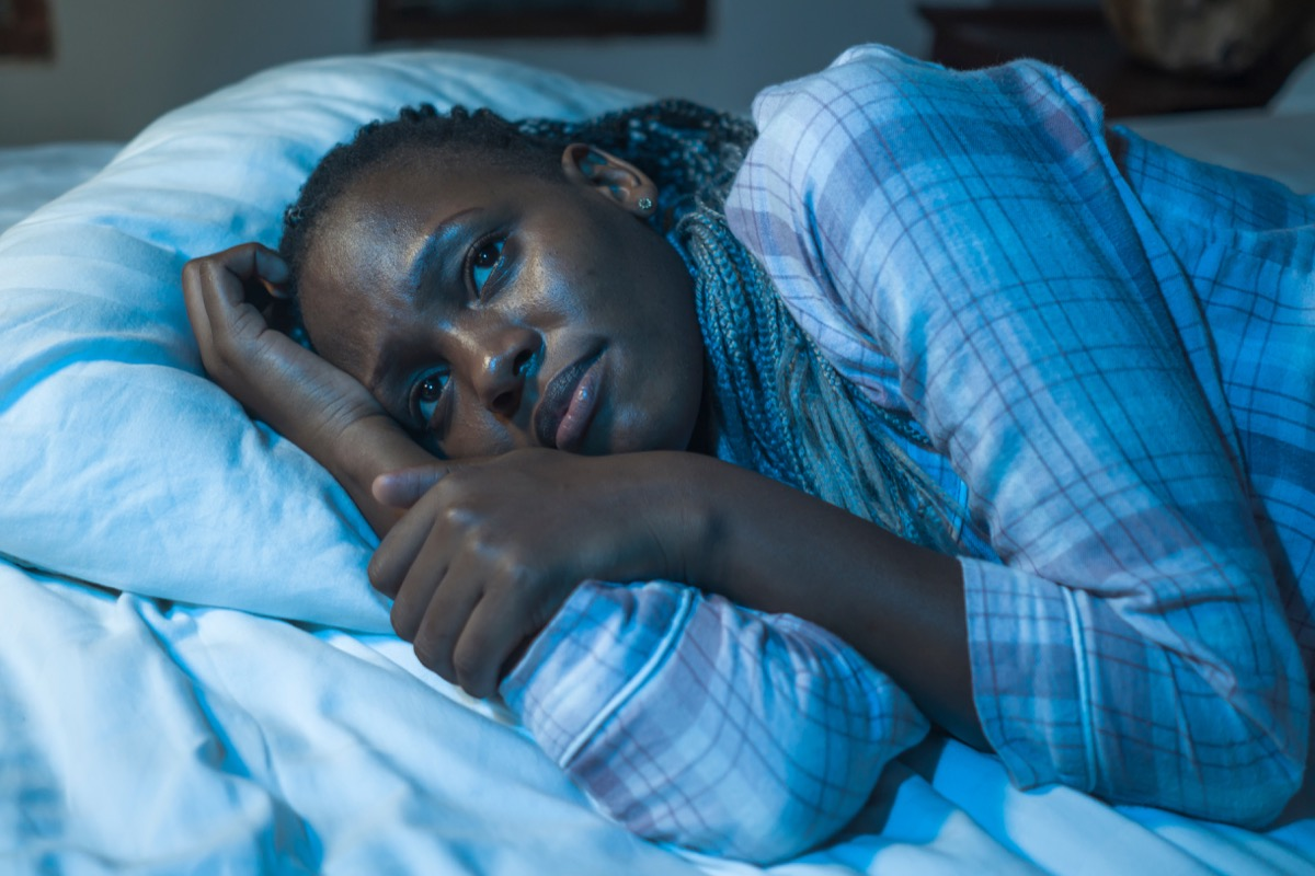 woman lying on bed at home unhappy and sleepless at night feeling overwhelmed suffering depression problem and insomnia