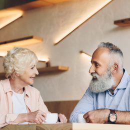 A senior man and woman having a conversation in a cafe