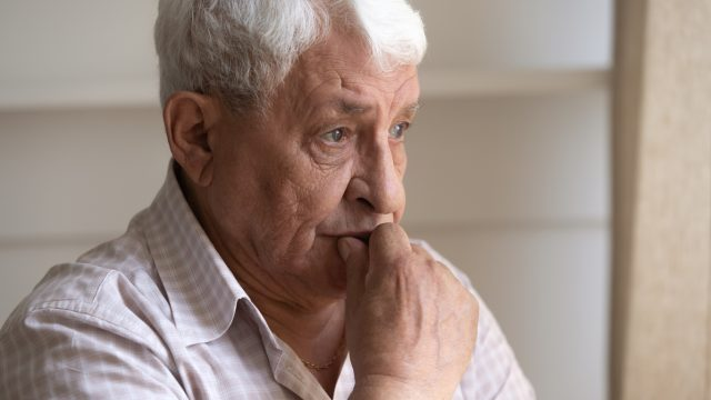 A senior man sitting with a concerned look on his face, potentially suffering from dementia