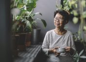 A senior woman drinking coffee while surrounded by houseplants