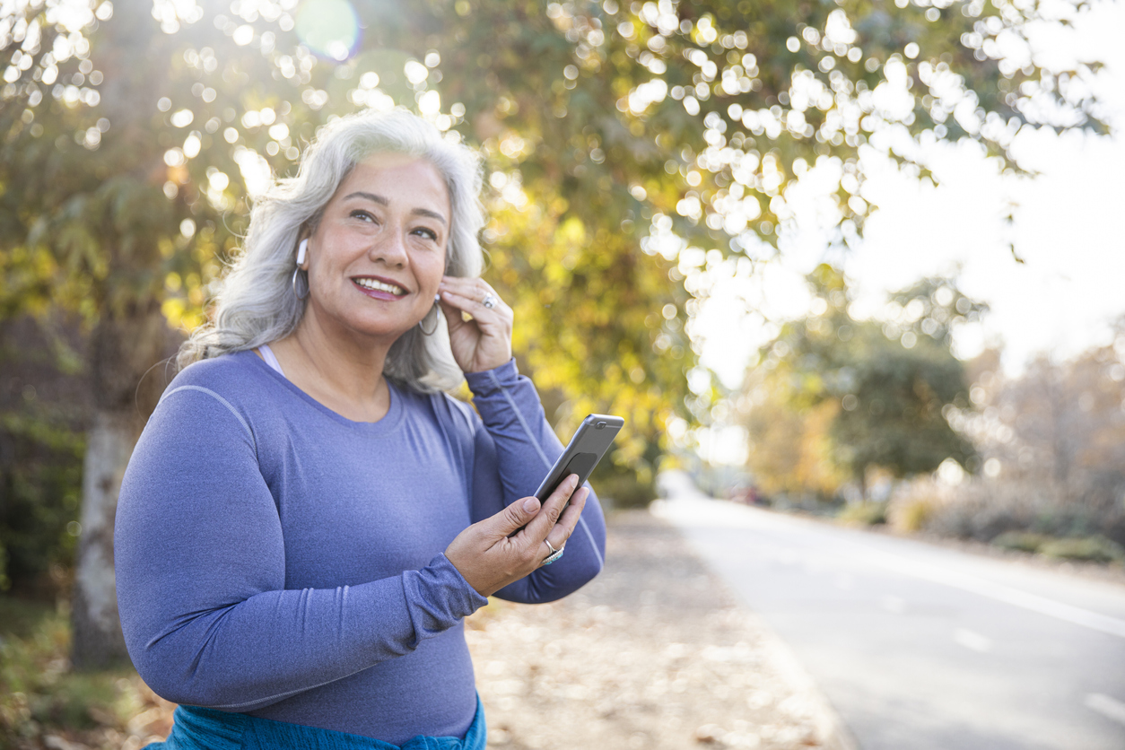 A senior woman putting in earbuds while getting ready to take a walk