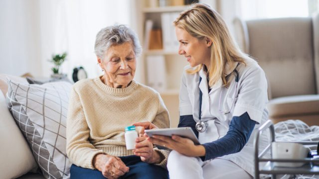 A senior woman speaking to a healthcare worker about medication