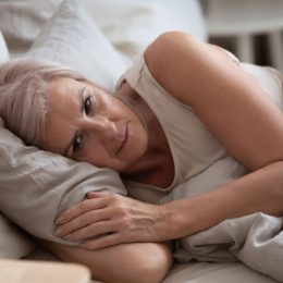 A senior woman lying awake in bed with a worried look on her face