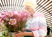 A senior woman smelling a bunch of flowers