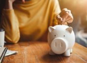 Woman putting money in piggy bank for retirement