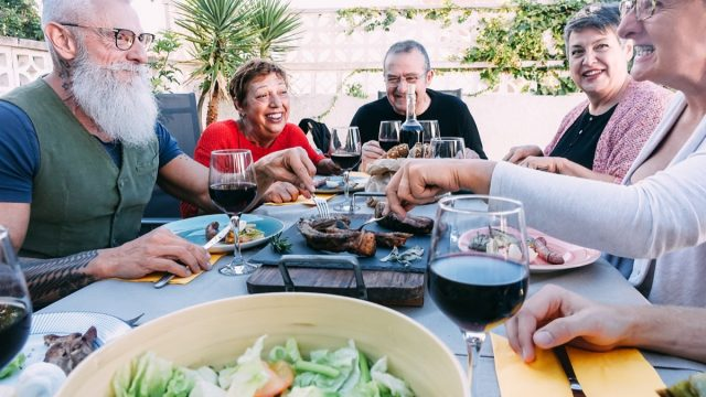 Happy senior friends eating at barbecue home backyard dinner – Mature people having fun at bbq meal in villa's patio – Summer lifestyle and food concept – Main focus on left hipster man face