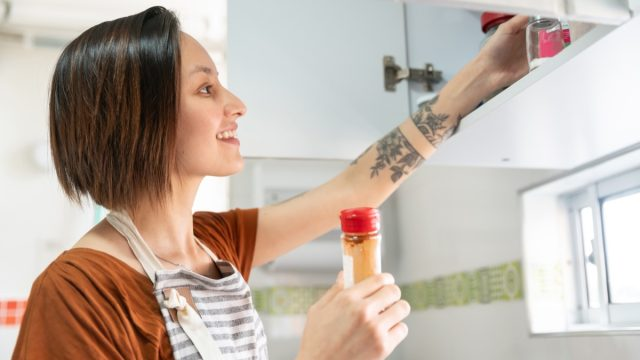 woman cooking at home and looking for some spices in the kitchen cabinet