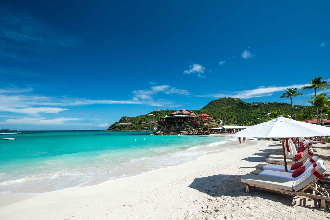 A white sand beach with lounge chairs in St. Barths