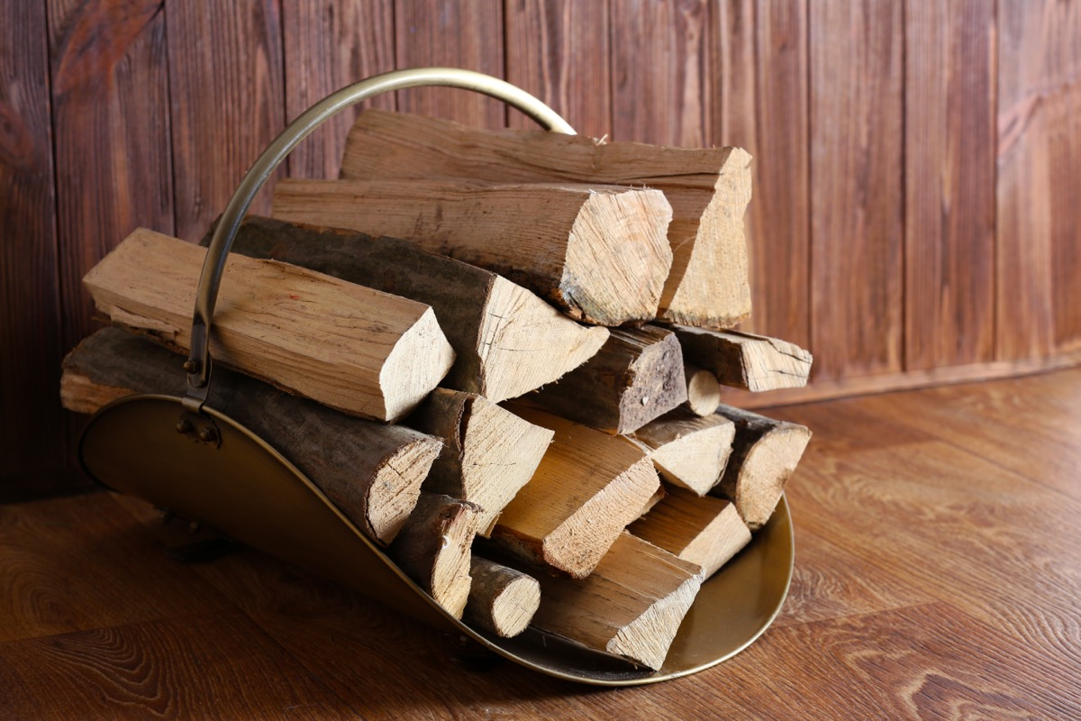 stacked firewood in metal carrier inside home