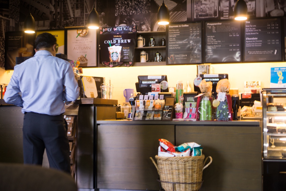 vKuala Lumpur, Malaysia - October 29 2017 : A Man stand to order beverages at Starbucks store in Putrajaya Government Office. Starbucks Corporation is an American coffee company and coffeehouse chain.