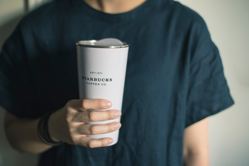 A person holding a reusable Starbucks thermal cup