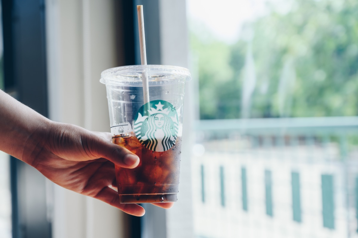 Chiang Mai, Thailand : 22/07/2020 : Someone holding a cup of Cold Brew coffee in Starbucks coffee shop. Cold brewing is a method of brewing that combines ground coffee and cool water.