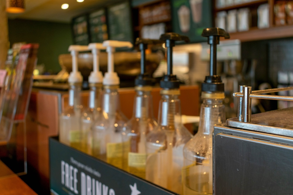 Durham, UK - 14th July 2019: Blurred photograph of Starbucks syrups with plastic lids and the counter in the background. Starbucks is a popular coffee chain across the world. Coffee café concept.